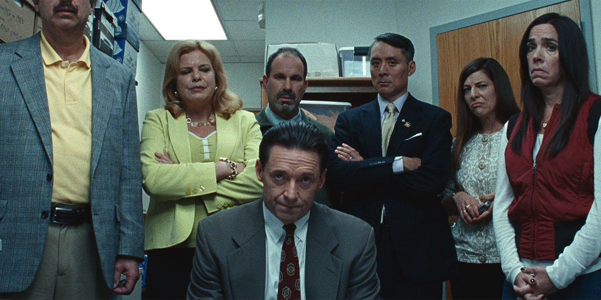 Hugh Jackman surrounded by other characters in the film Bad Education.