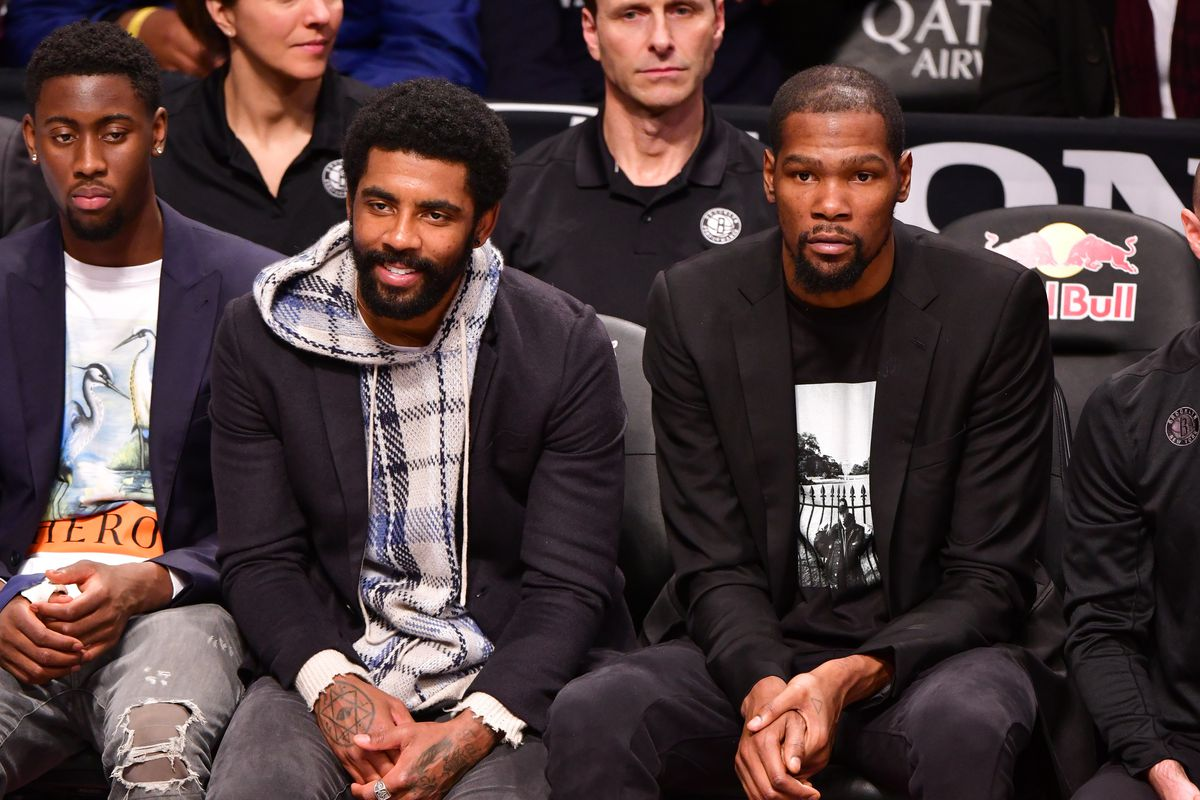 Kyrie Irving and Kevin Durant attend Philadelphia 76ers v Brooklyn Nets game at Barclays Center on December 15, 2019 in New York City.
