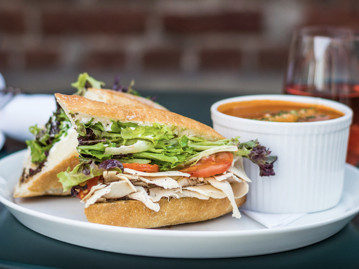 A photo of a roasted turkey sandwich and a cup of tomato soup from Vert Kitchen