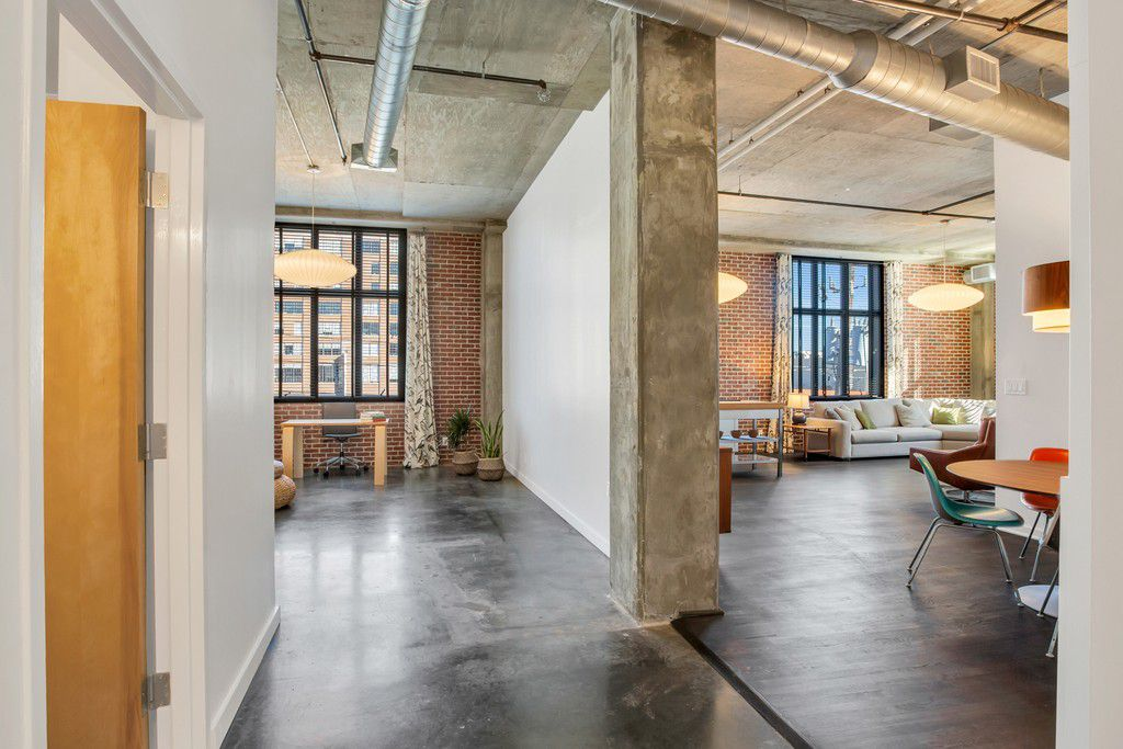 A loft with ductwork and concrete overhead and wood floors.