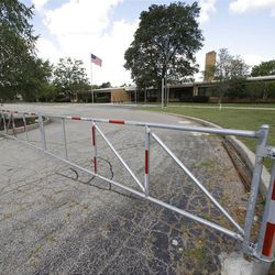 """A gate is shown outside the former Eagle Elementary School in West Bloomfield, Mich., Wednesday, Aug. 29, 2012. This affluent Detroit suburb with a diverse mix of religions and races and center of the region's Jewish community is the latest battleground over mosque construction, as some residents push back against a school district's decision to sell a vacant elementary school to an Islamic group. The Farmington Hills school district defends its agreement to sell Eagle Elementary School to a Muslim association and an administrator says opposition now can be classified as """"Islamophobia."""" (AP Photo/Paul Sancya)"""