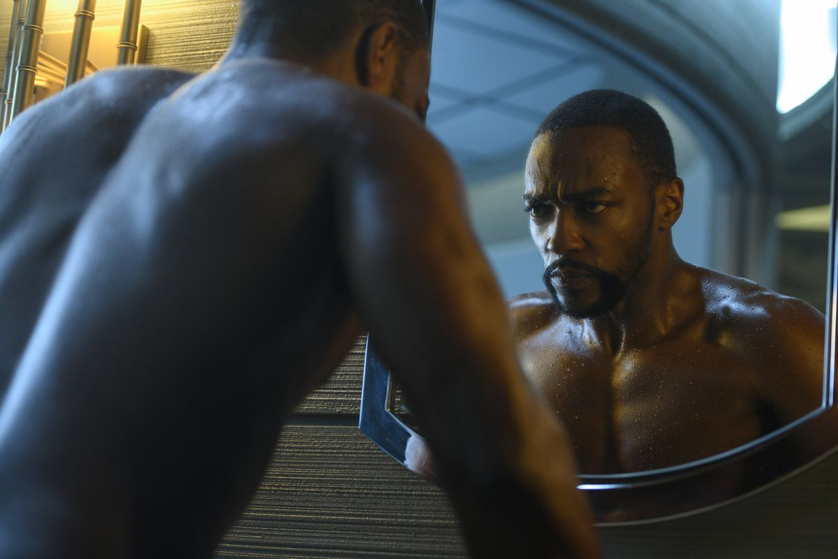 Anthony Mackie as Takeshi Kovacs looks at his new sleeve in the mirror.