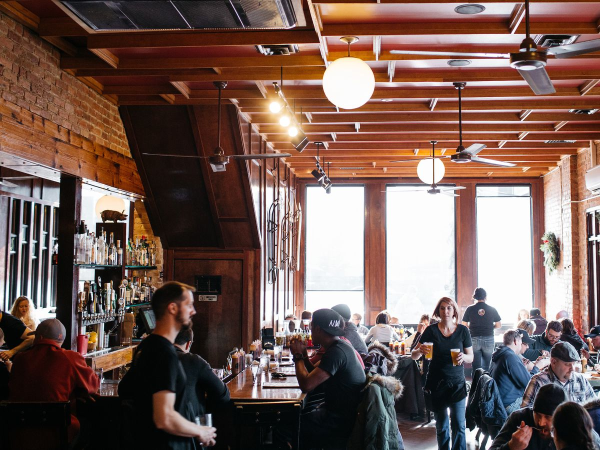 Customers fill tables inside the brick and wood dining room at Slows in Corktown as waiters in black shirts walk by with pints of beer in hand.