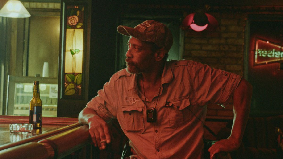 A man sits at a bar, bathed in low light.