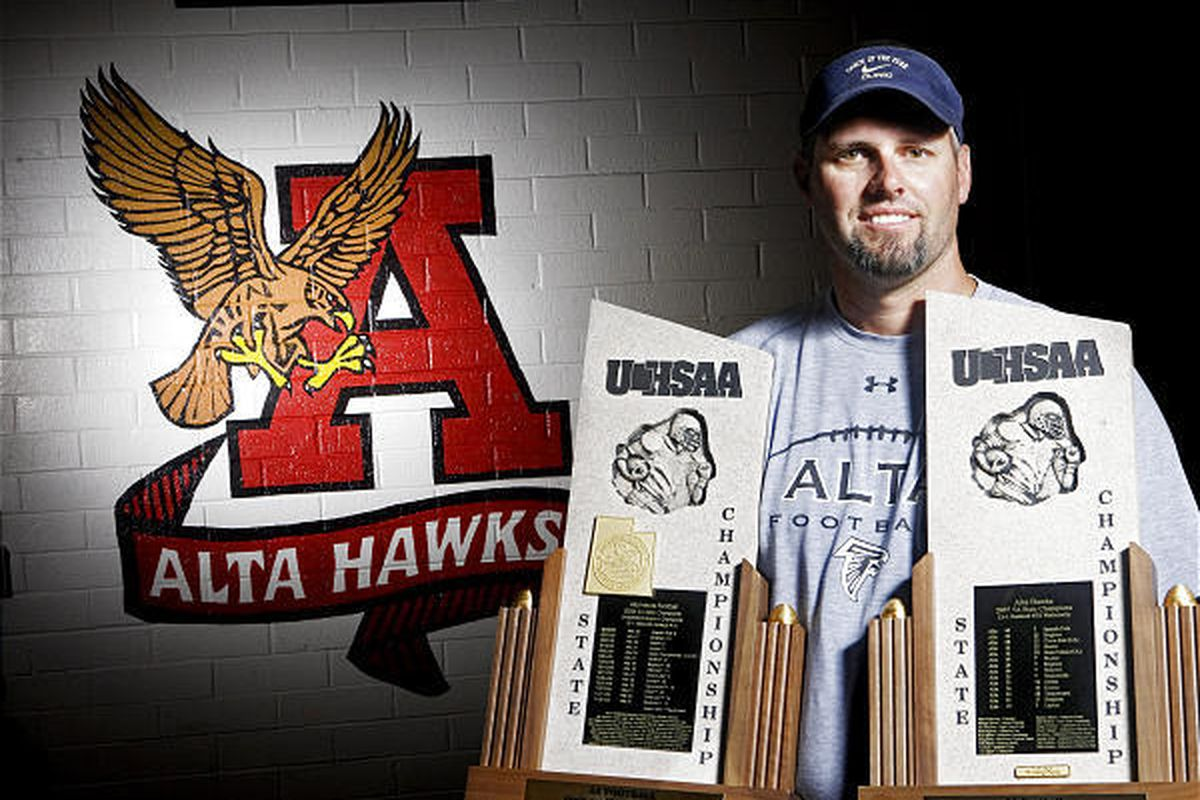 Alta head football coach Les Hamilton holding 2 state championship trophies at Alta High School August 11, 2010.