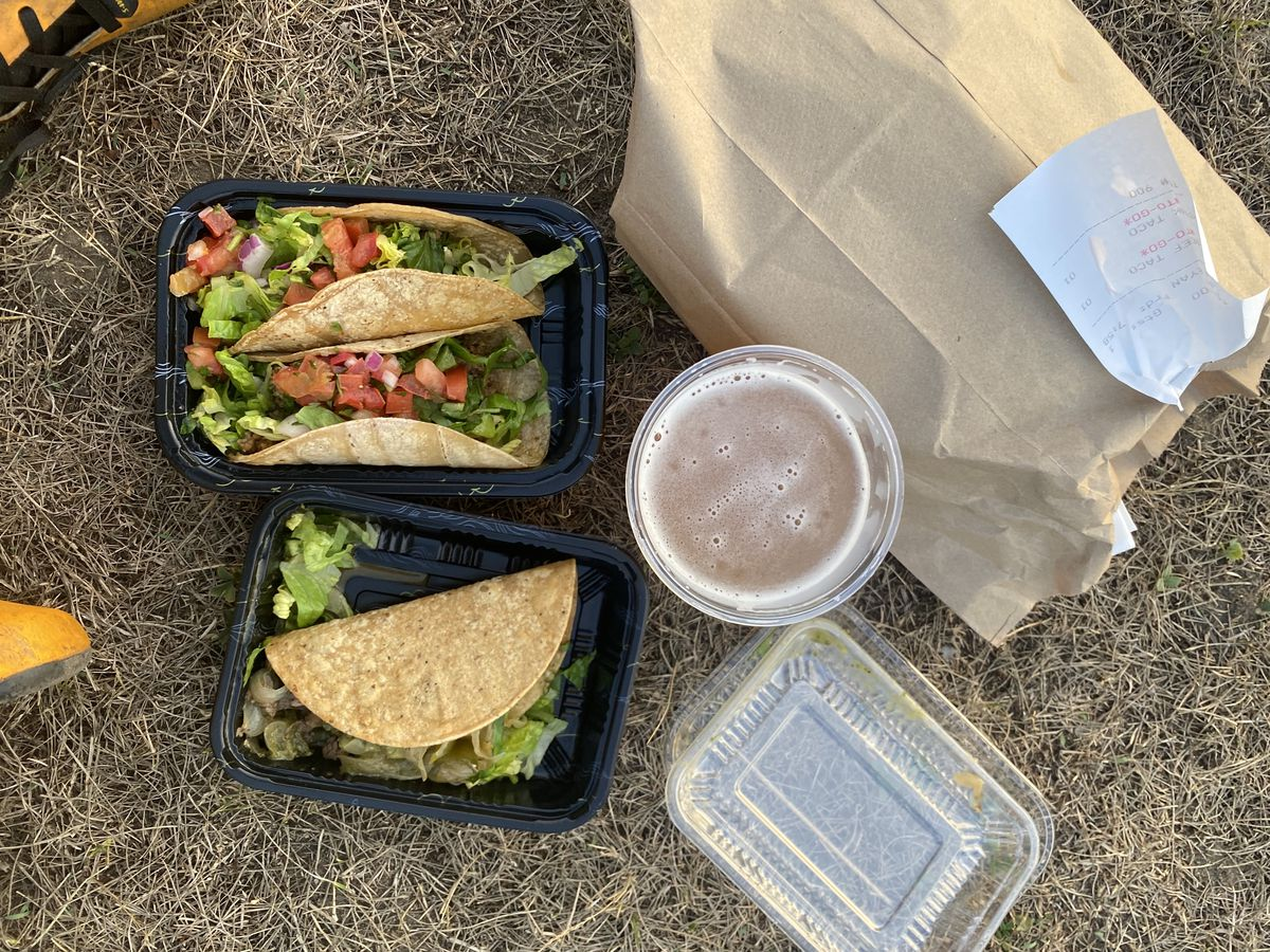 Soft beef tacos and a crispy steak taco from Taco Dive Bar sit in takeout containers on the Peekskill waterfront