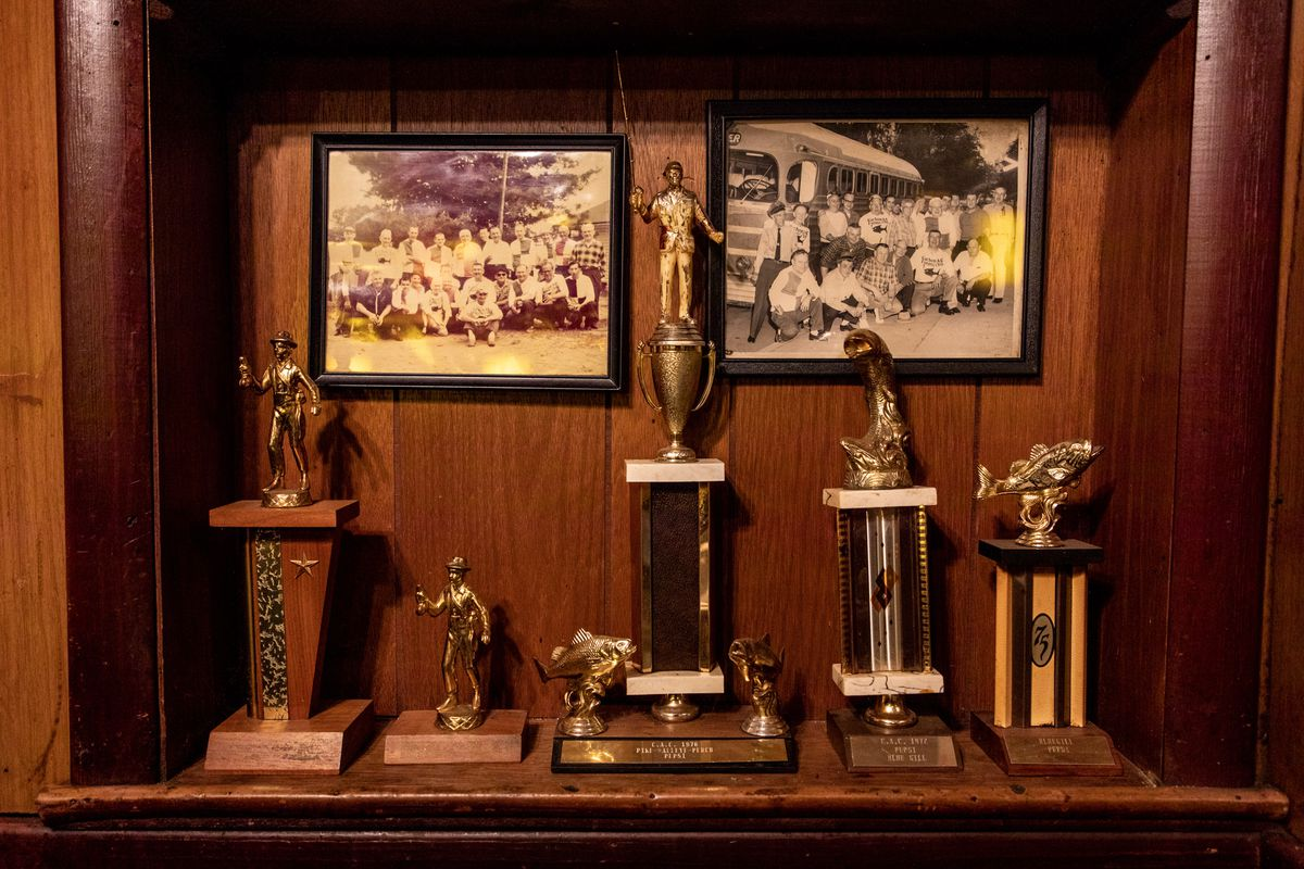 Trophies and old photos of CAC members rest in a wood-paneled alcove.