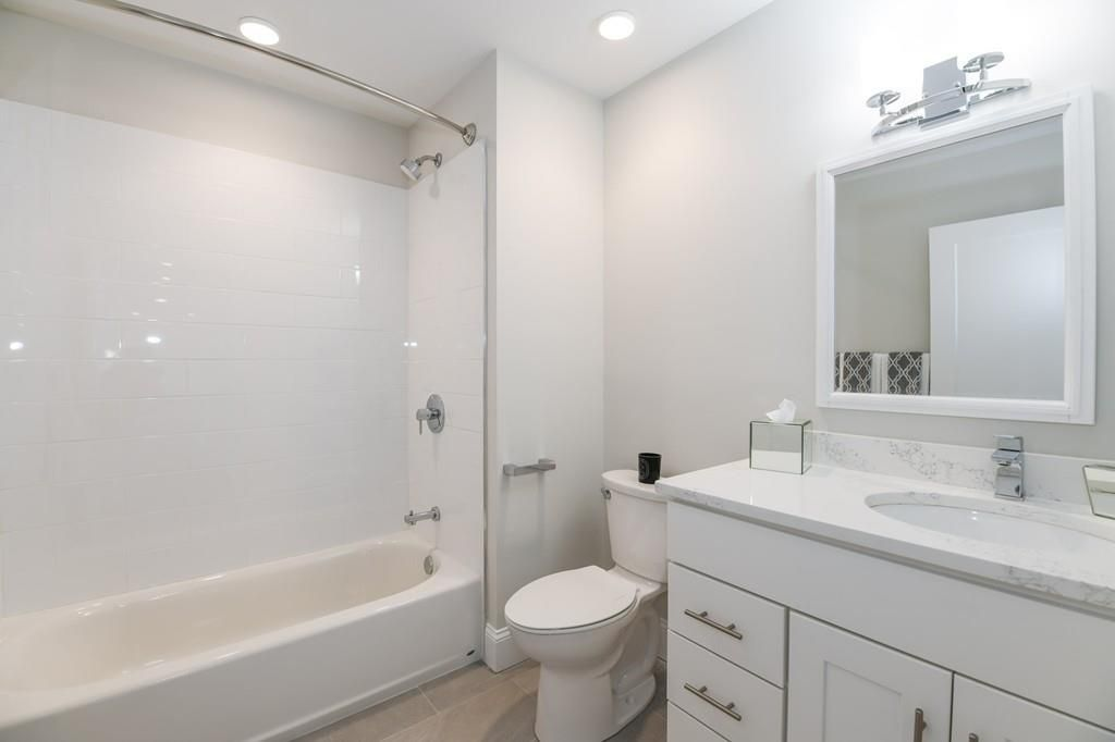 A bathroom with no curtain on the shower.