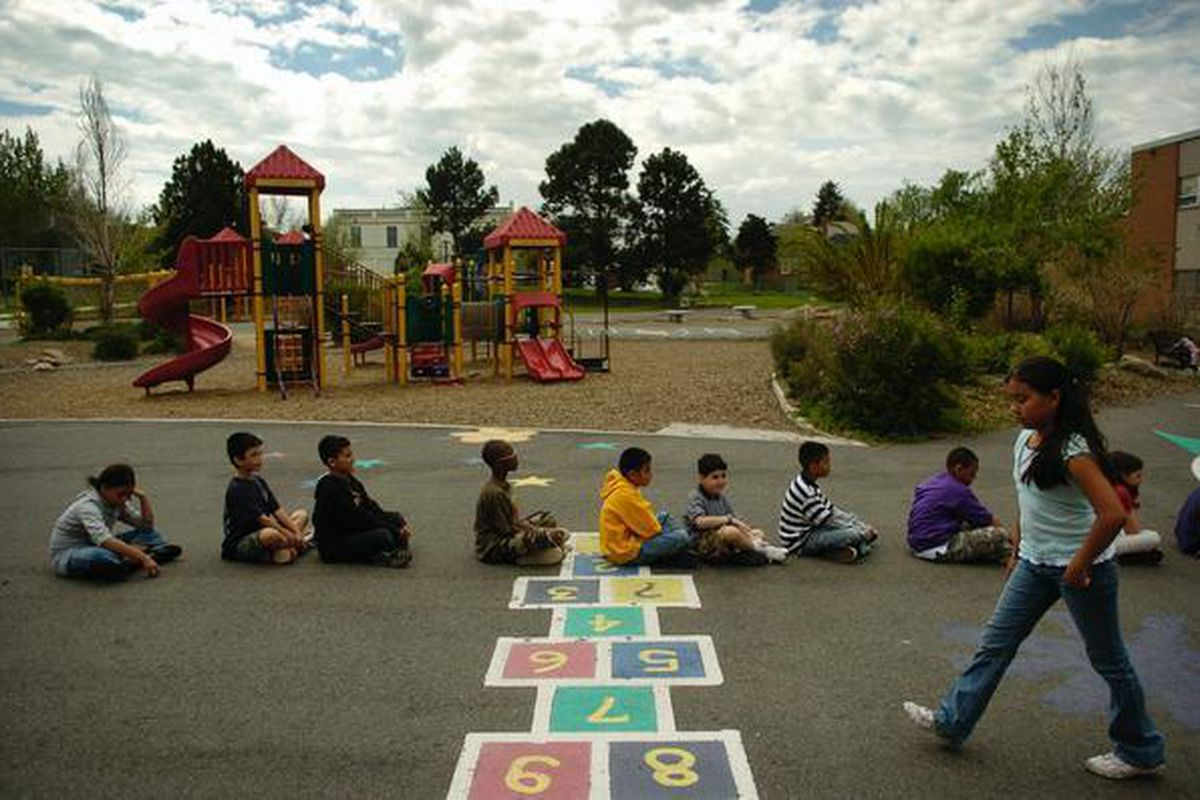 Fourth-graders at Whittier ECE-8 School sit in a line on the playground.