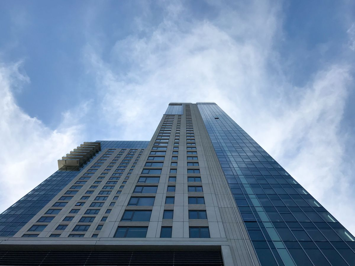 An up-close, neck-craning look at a glassy apartment tower.
