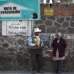 Residents stand next to an evacuation route sign in the village of Xalitzintla, Mexico, Friday, April 20, 2012.  A roiling white cloud of ash, gas, water vapor and superheated rock spewed from the cone of Popocatepetl high above the village, whose residents said they were awakened by a window-rattling series of eruptions.  (AP Photo/Dieu Nalio Chery)