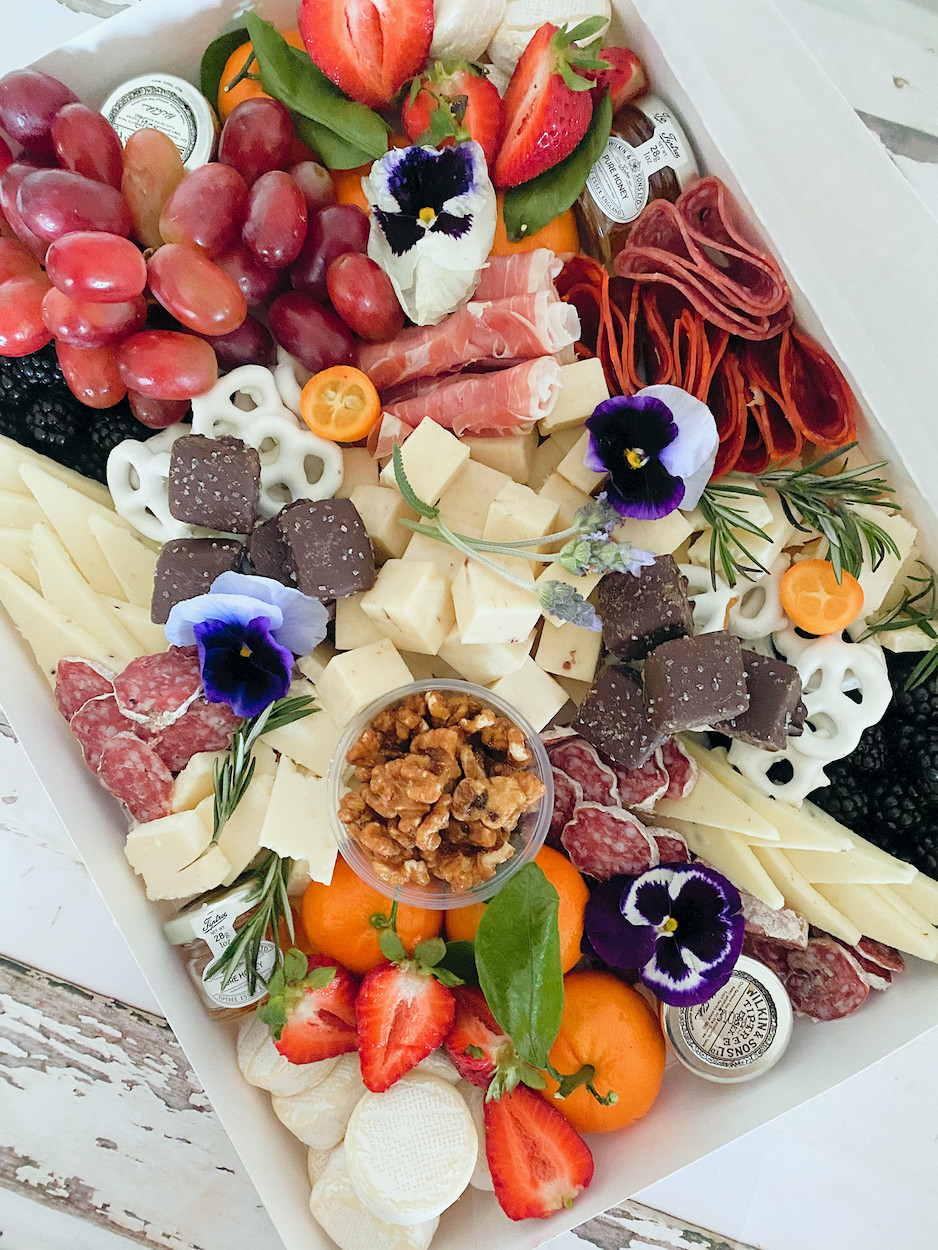 A grazing board of cured meats, cheese, fruit, and chocolate covered pretzels with a few flowers