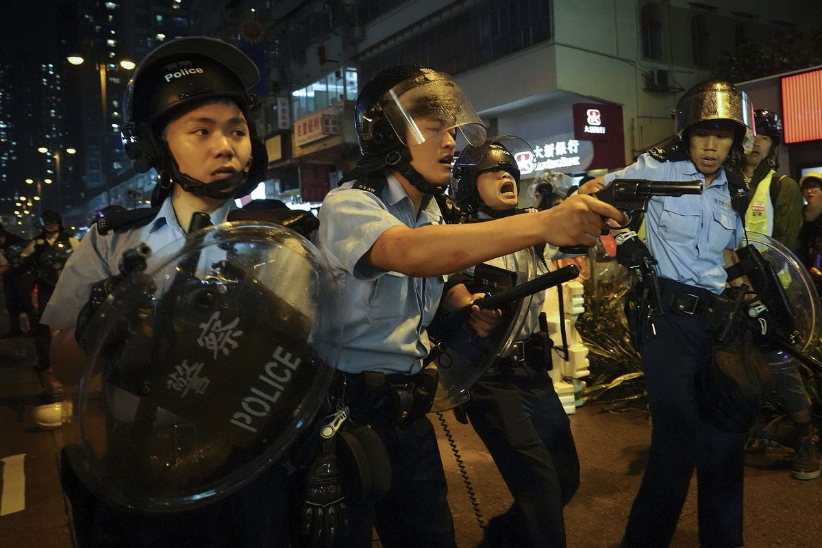 Policemen pull out their guns after a confrontation with demonstrators during a protest in Hong Kong, Sunday, Aug. 25, 2019. Hong Kong police have rolled out water cannon trucks for the first time in this summer's pro-democracy protests. The two trucks mo