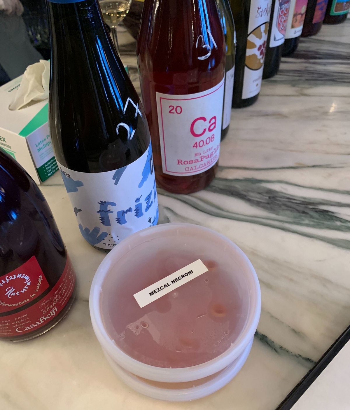 """In the foreground, a plastic to-go container with a printed label """"Mezcal Negroni"""" sits on a marble countertop. Behind it, bottles of wine are lined up for sale."""