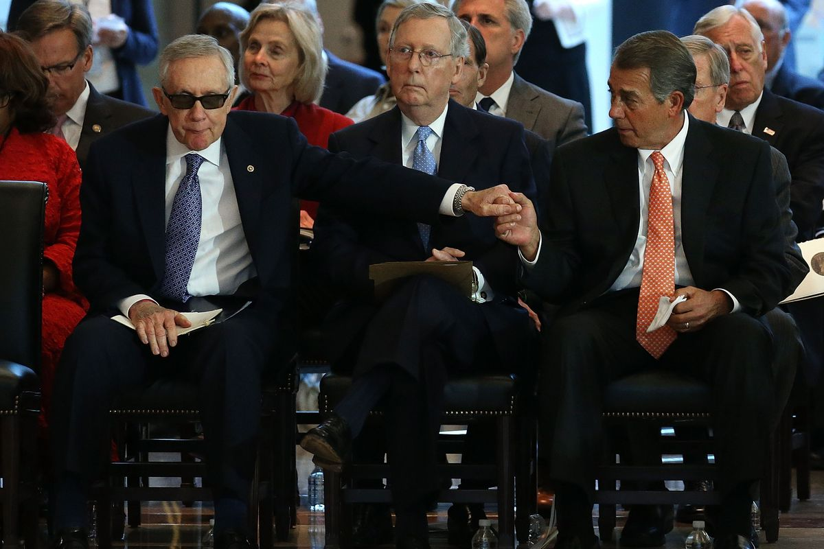 Senate Minority Leader Harry Reid (D-NV) (L) reaches out to House Speaker John Boehner (R-OH) (R) as Senate Majority Leader Mitch McConnell (R-KY) (C) looks on during a ceremony on Capitol Hill July 8, 2015, in Washington, DC.