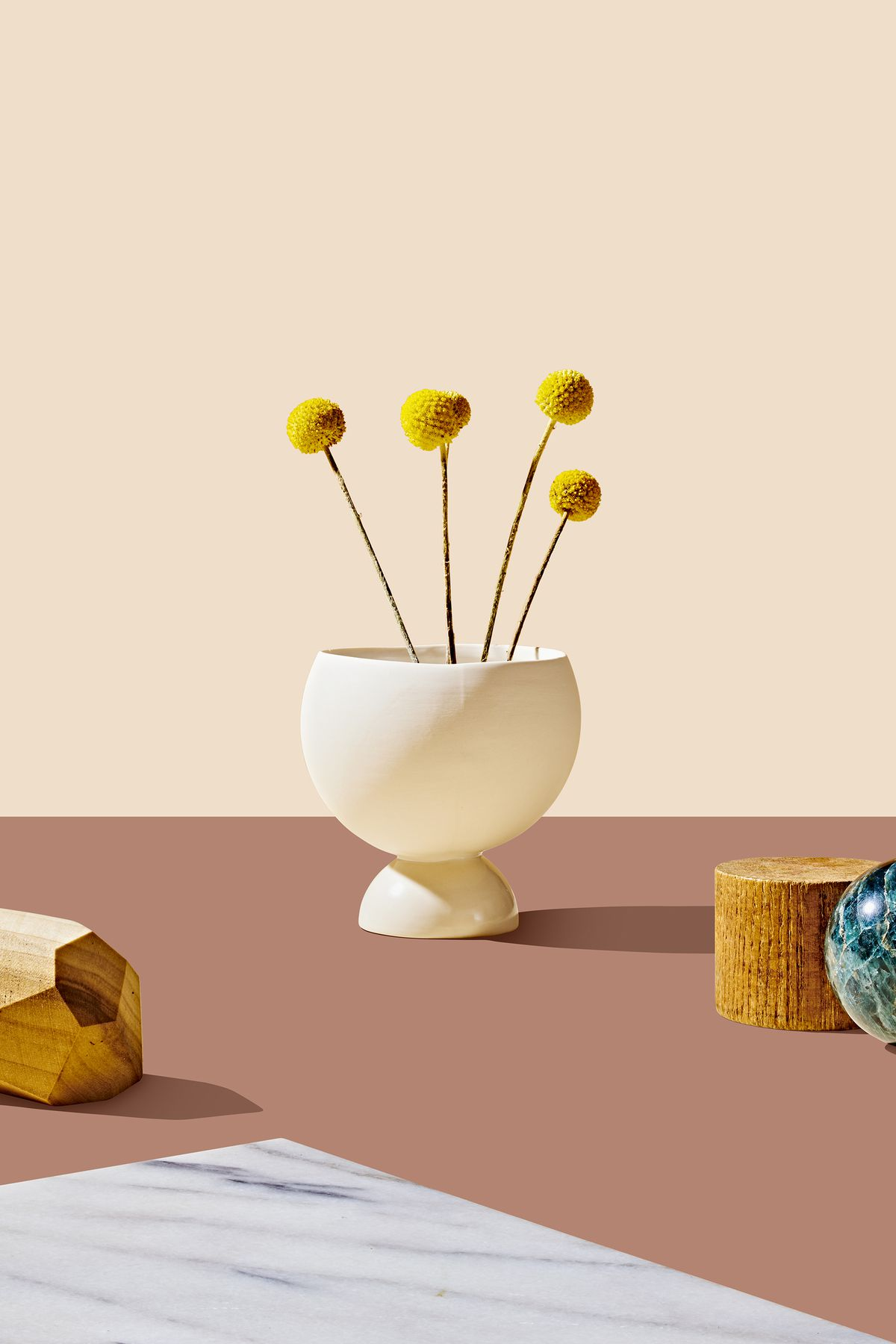 A white stoneware vase with yellow flowers. This is part of the 2019 Holiday Gift Guide for Curbed. The vase is sitting on a flat mauve surface and is flanked by various design objects.