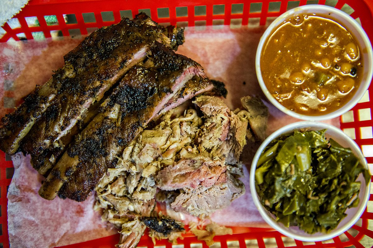 A plate of ribs, chopped whole hog, barbecue beans, and greens.