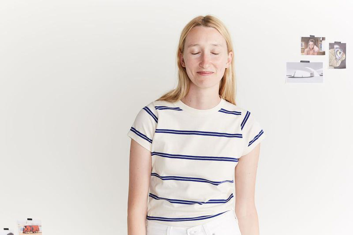 A blonde woman wears a white and blue striped T-shirt.