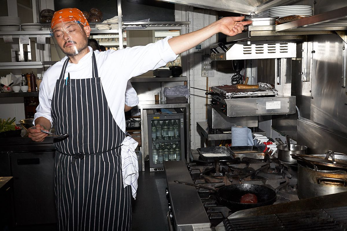 A chef in the kitchen of St. John Bread and Wine, wearing a face visor to protect against the transmission of COVID-19