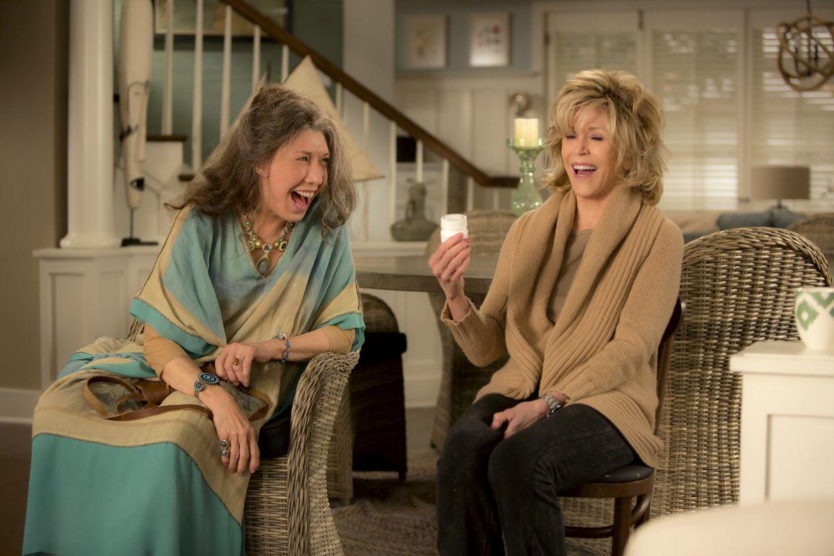 Lily Tomlin e Jane Fonda sono sedute una accanto all'altra e ridono. Jane fonda sta fissando un barattolo bianco che tiene in mano. E' il primo episodio di Grace e Frankie, una serie originale Netflix.