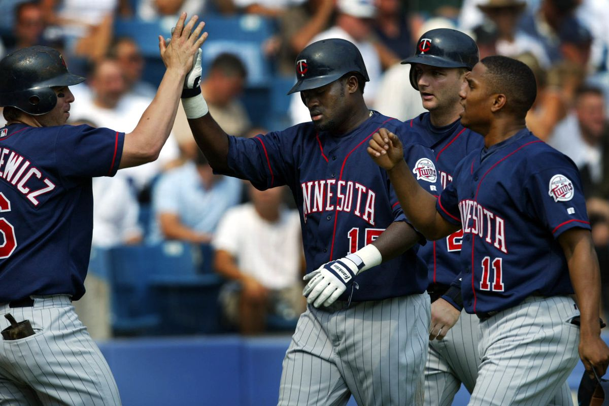 83427----Chicago IL, Twins vs White Sox 9/11/03---- Doug Mientkiewicz high fives teamates Cristian Guzman, Jacque Jones and A.J. Pierzynski after they scored on a double by Shannon Stewart and a throwing error by Sox centerfielder Carl Everett in the 3rd