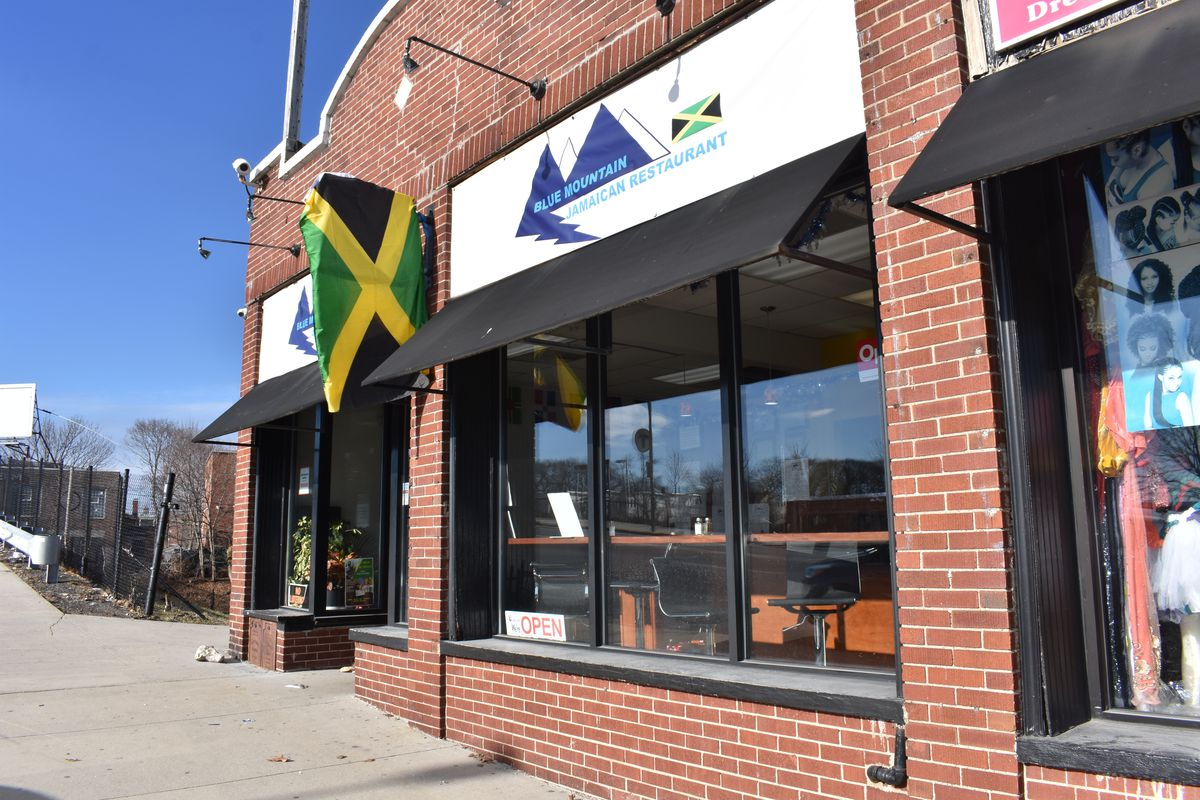 The facade of brick building with a Jamaican flag hung above the entryway. Bright blue sky in the background.