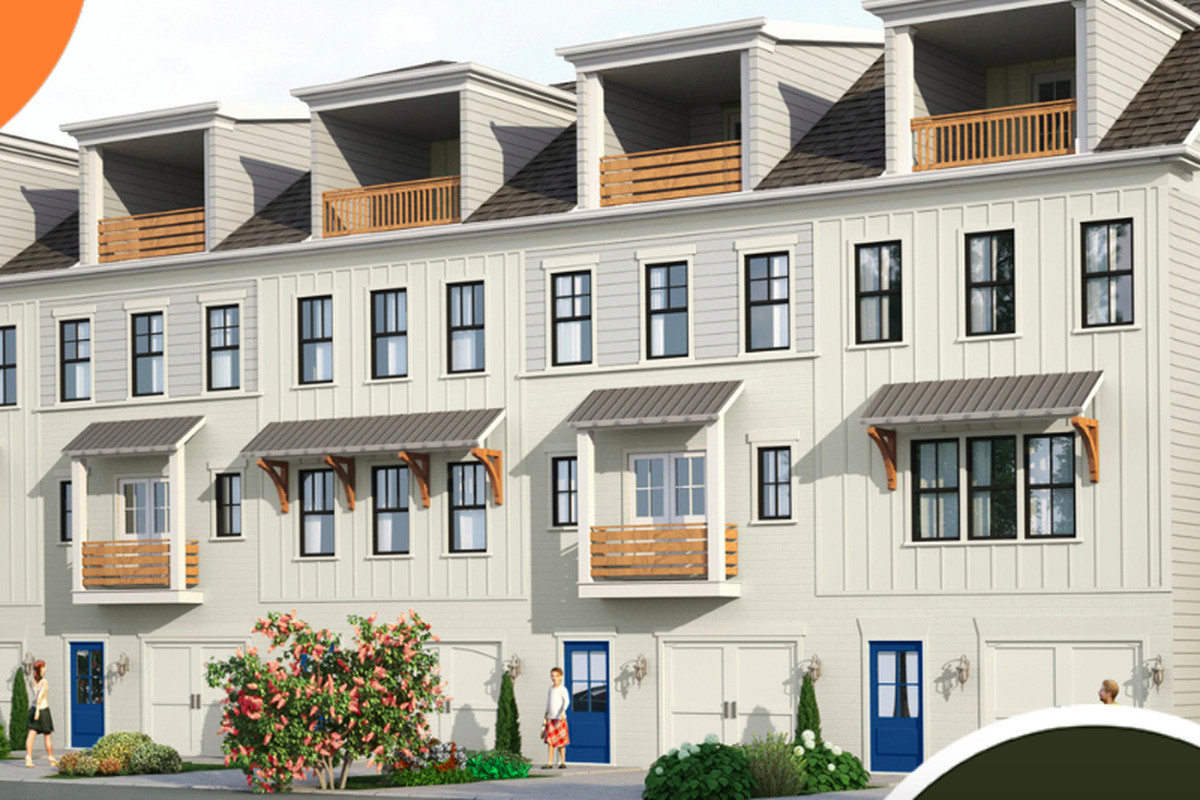 A row of white townhomes with balconies up top.