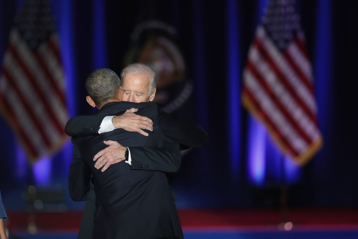 President Barack Obama, with his back to the camera, embraces Vice President Joe Biden on a darkened stage with American flags standing in the background.