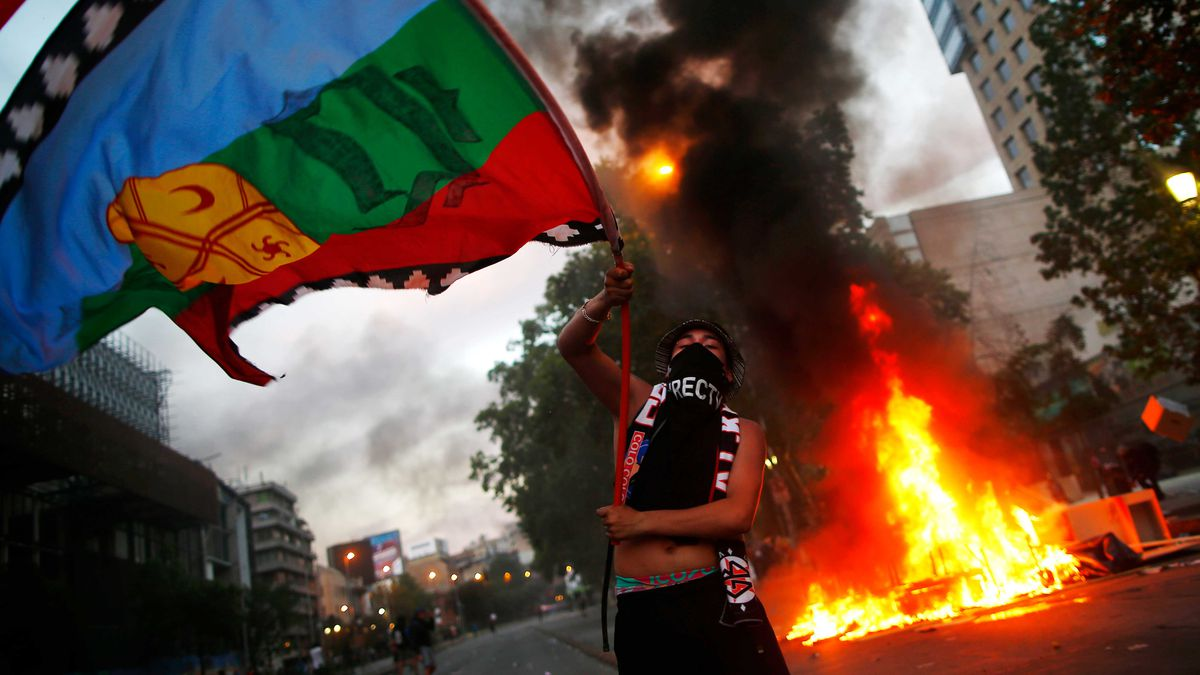 A protester waves a large flag in front of a fire on a city street.