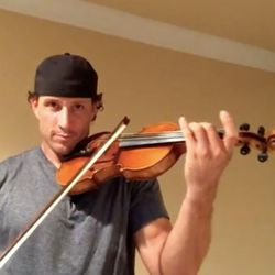"""John Denney plays his violin in a video on SI.com in a competition for """"Football's Most Valuable Performer."""""""