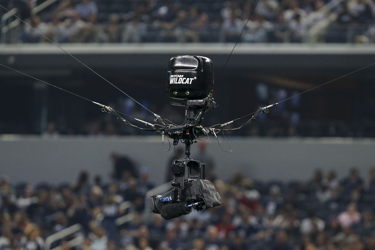 A camera suspended on wires in an NFL stadium