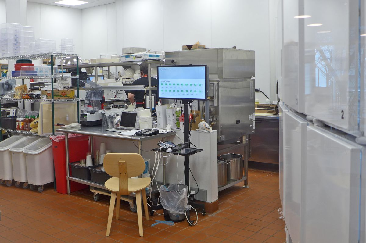 A cluttered kitchen with computer screens.