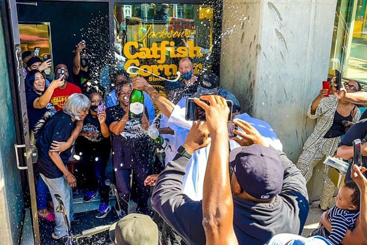 A crowd celebrates with sprays of champagne outside Jackson's Catfish Corner on Jackson Street in the Central District.
