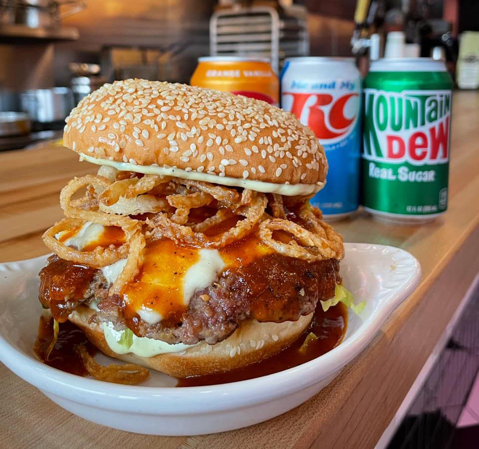 An overflowing burger with fried onions, cheese, and sauce melting over a patty and onto the dish below. The dish sits on a wood counter with cans of soda in the background