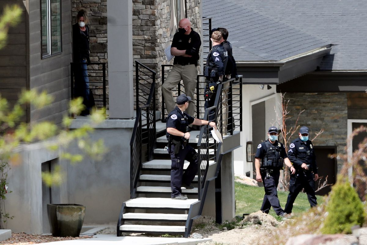 South Jordan police detectives stand on the front steps before going inside to investigate a suspicious body at a home in a gated community in the 10200 South block of Jordan Creek Drive on Monday, April 20, 2020.