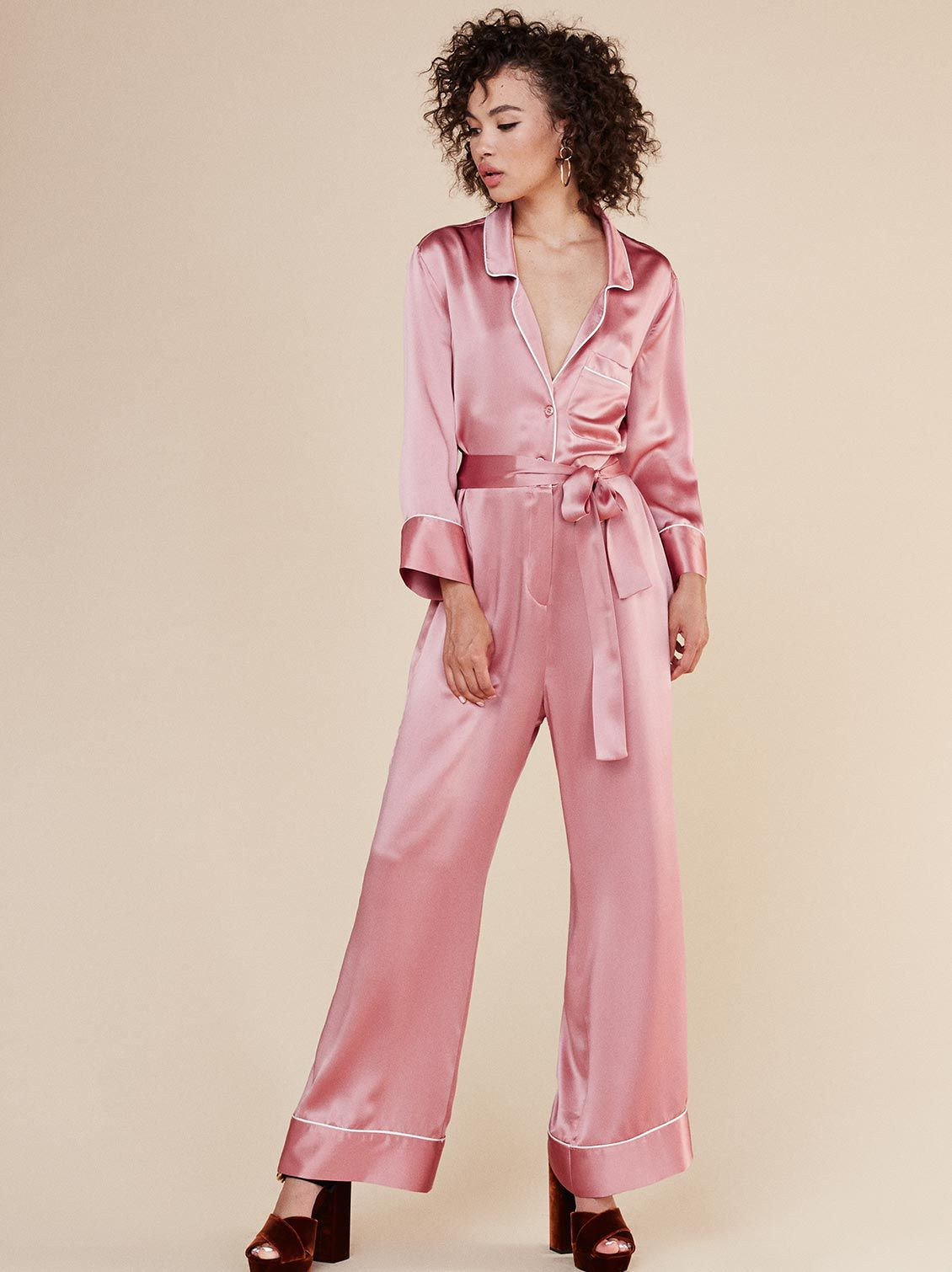 A model wearing a pink satin jumpsuit that looks like pajamas