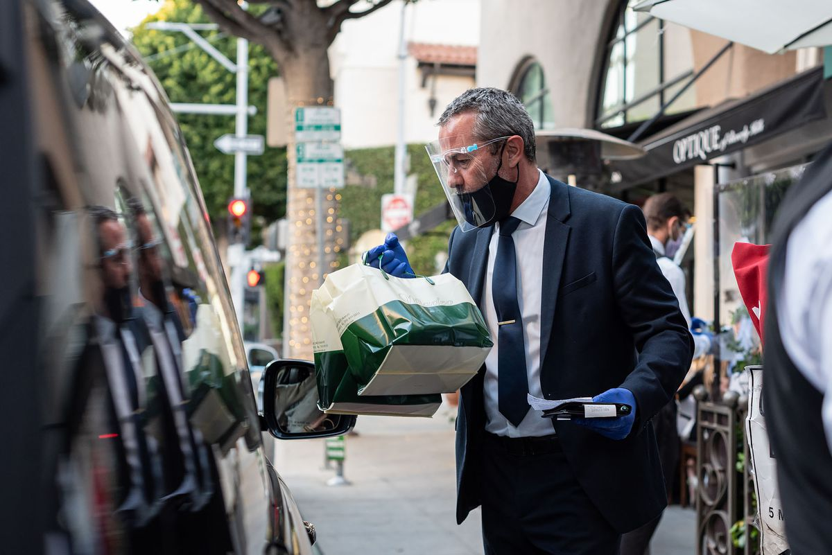 An employee in a suit drops off food into a car in front of a restaurant.