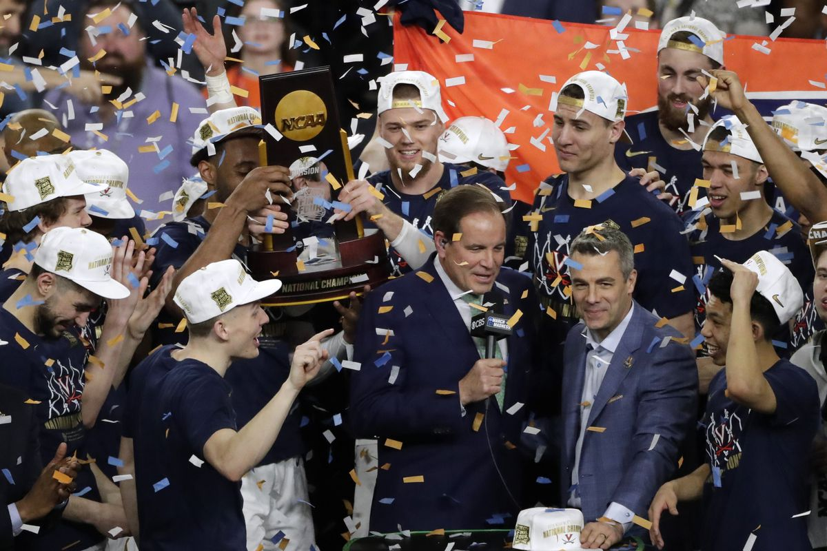 Virginia head coach Tony Bennett, right, celebrates with his team after the championship game against Texas Tech in the Final Four NCAA college basketball tournament, Monday, in Minneapolis. Virginia won 85-77 in overtime.