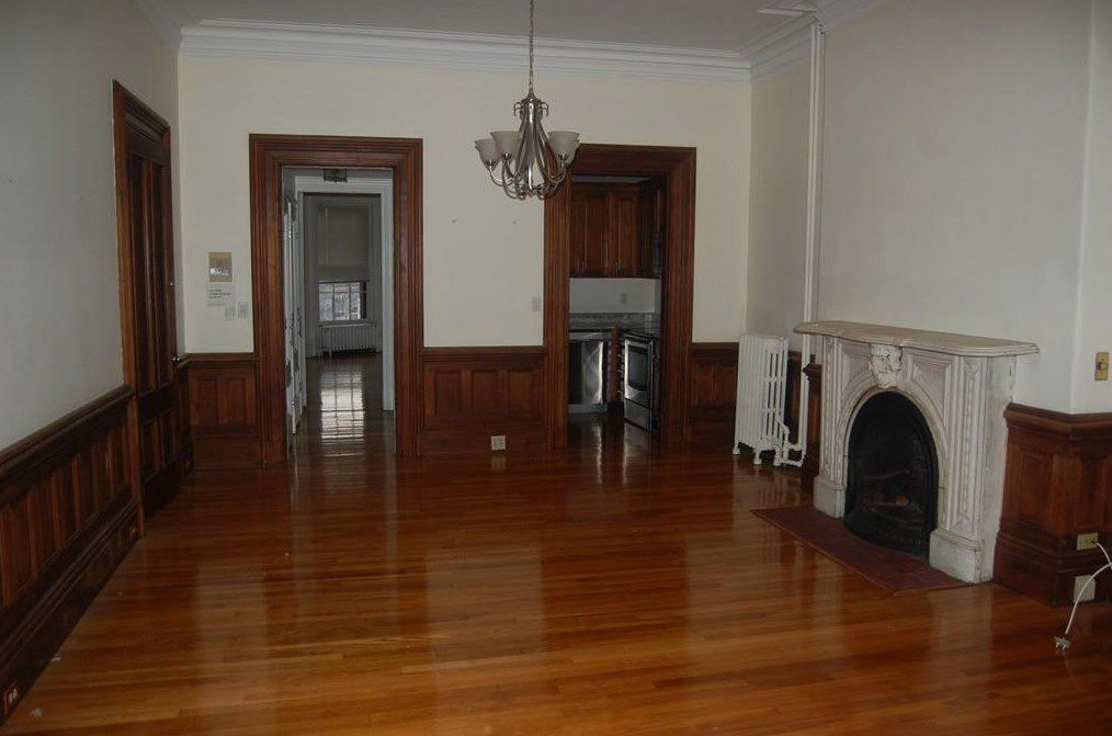An empty living room with two doors leading out of it, and there's a big stone fireplace.