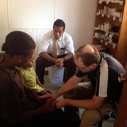 With the help of an LDS missionary acting as his translator, Dr. Matthew Cornish treats a Vanuatuan woman and her child.