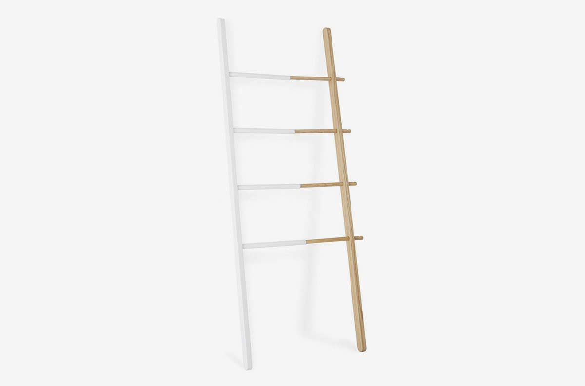 A ladder with one side dipped in white paint.