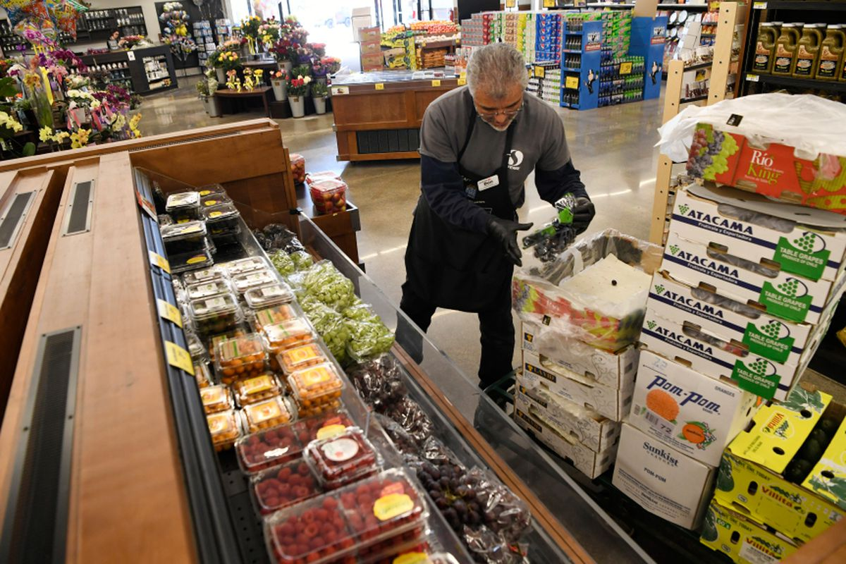 A man stocks grapes and strawberries in a grocery store.