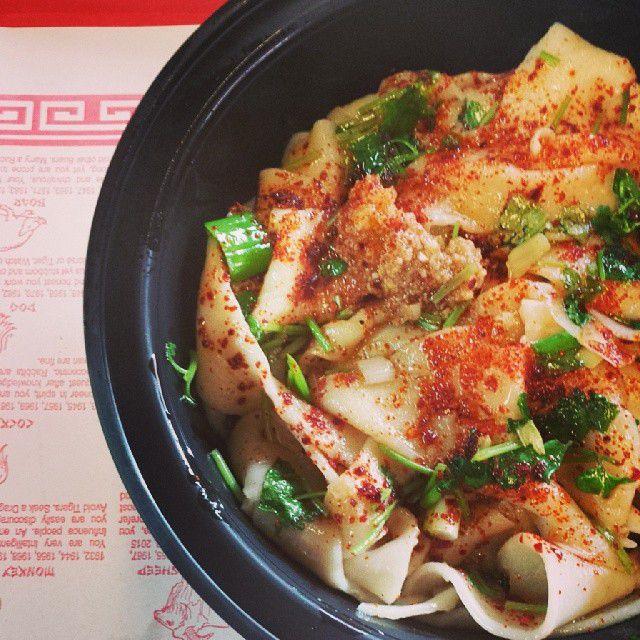 A black plastic bowl holds thick hand-pulled Xi-an style noodles topped with scallions, garlic, and chili. The bowl sits on a paper placemat covered with red text.