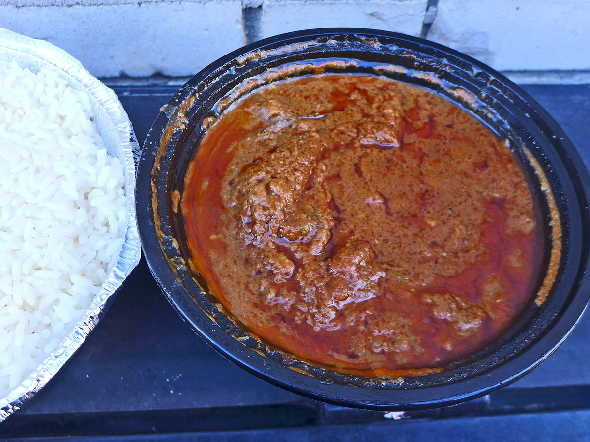 Brown bumpy stew in one container, white rice in the other.
