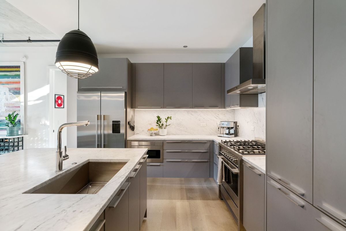 The open kitchen with a large marble island, grey cabinets, and stainless steel appliances.