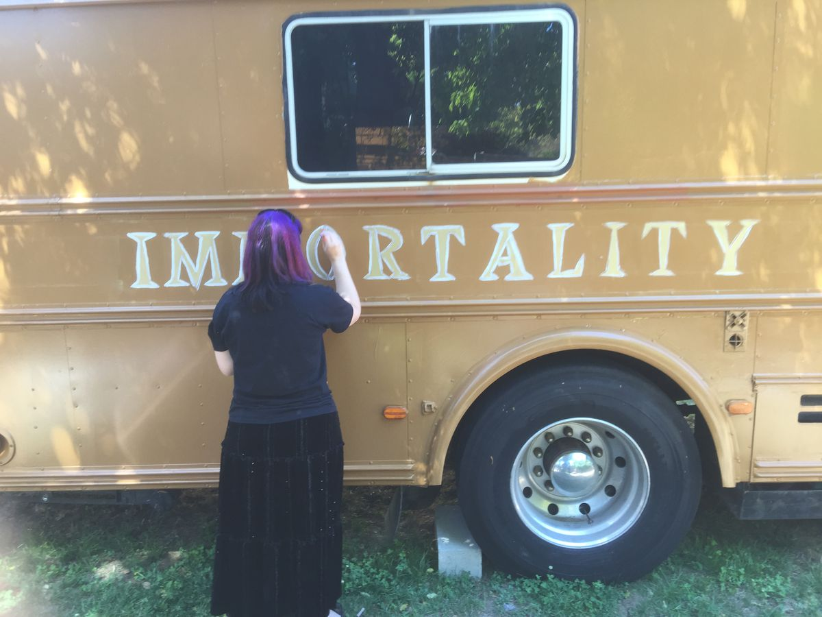 """Woman in purple hair paints white outlines around the words """"Immortality"""" on a yellowish orange bus."""