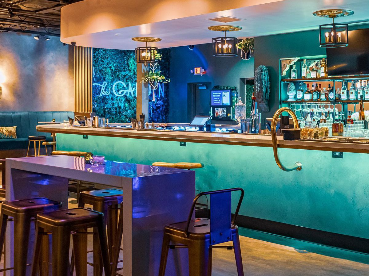 A pretty green bar with a high-top table and stools in front of it.