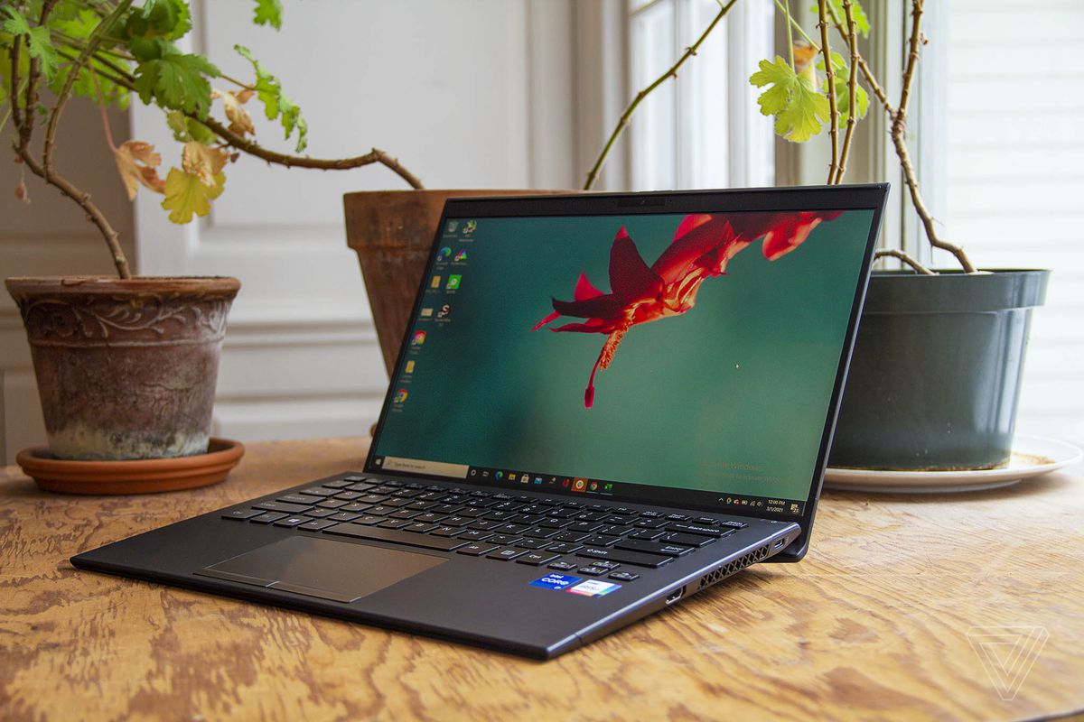 The Vaio Z on a table with three potted plants in the background, open and angled to the left. The screen displays a red flower on a blue background.