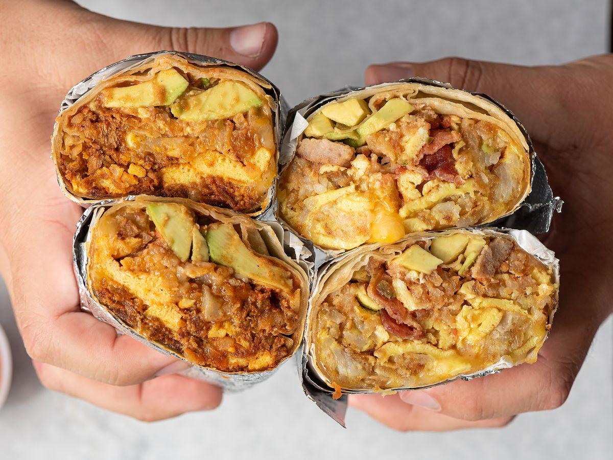 Holding breakfast burritos, cut in half.
