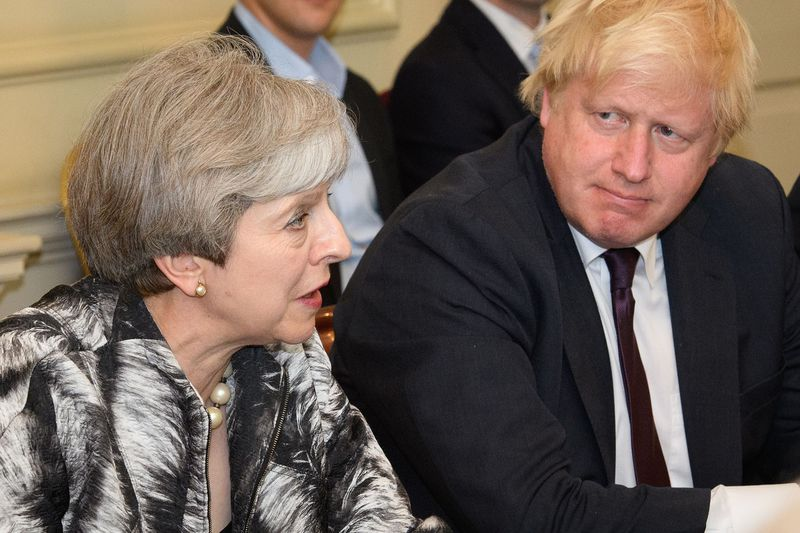 Prime Minister Theresa May (L) sits with then-Foreign Secretary Boris Johnson during the first Cabinet meeting of May's new team at 10 Downing Street in London on June 12, 2017.